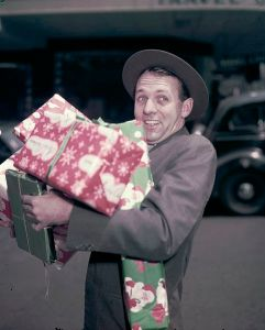 481px-Man_with_Christmas_presents,_by_Jack_Hickson,_02_Nov_1957_(11426997875)